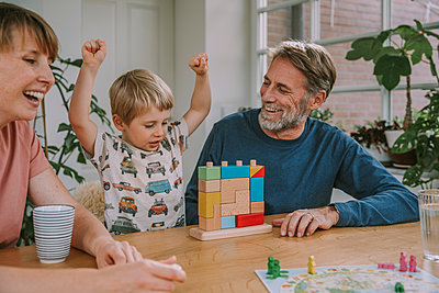 Mother and father playing with cheerful son toy block puzzle at home - p300m2226912 by Mareen Fischinger