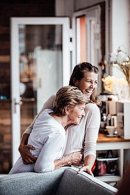 Cheerful young woman hugging grandmother while looking away - p300m2274963 by Gustafsson