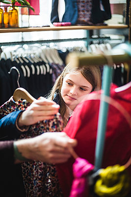 Cute girl looking at dress while shopping in boutique - p426m2097588 by Maskot