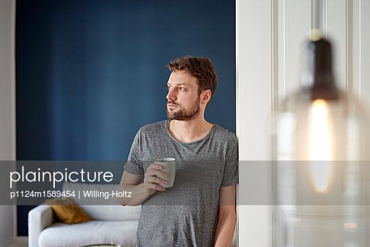 Junger Mann trinkt einen Becher Kaffee zuhause - p1124m1589454 von Willing-Holtz