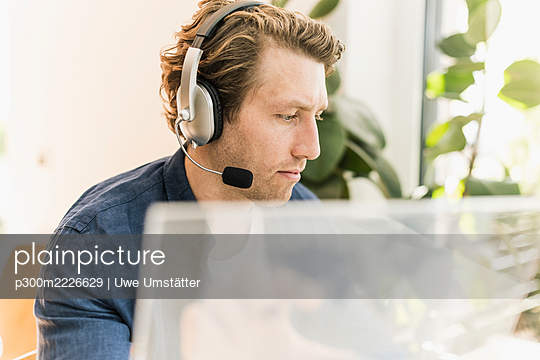 Man wearing headphone looking away while sitting at home - p300m2226629 by Uwe Umstätter