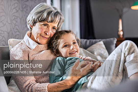 Girl relaxing with senior woman on sofa in living room - p300m2287435 by Stefanie Aumiller