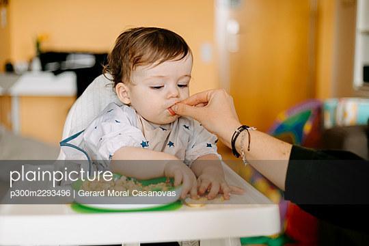 Mother feeding baby boy at home - p300m2293496 by Gerard Moral Casanovas