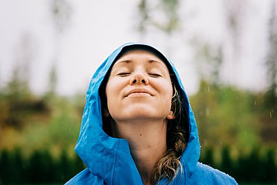 woman stood in the rain smiling with rain drops on her face - p1166m2193798 by Cavan Images