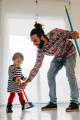 Happy father and little daughter sweeping the floor of the living room at home - p300m2103997 by Josep Rovirosa