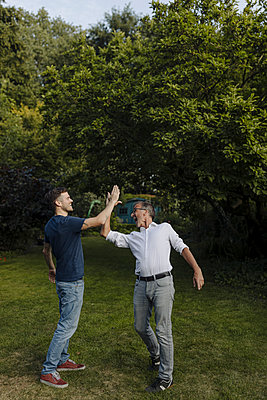 Laughing father and son doing high-five while standing in back yard - p300m2274967 by Gustafsson