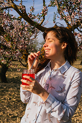 Smiling woman having strawberry soda at almond trees - p300m2275999 by Mar