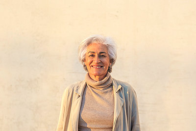 Mature woman smiling in front of wall - p300m2281480 by PICUA ESTUDIO