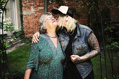 Daughter kissing mother while standing in back yard - p301m1130889f by Paula Winkler