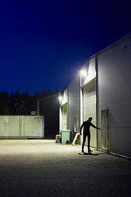 Man opening warehouse back door at night - p312m993144f by Jan Tove