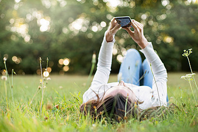 Young woman using smart phone while lying in park, Orgeval - p623m2294821 by Gabriel Sanchez