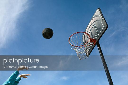 Basketball in air against blue sky - p1166m2191946 by Cavan Images