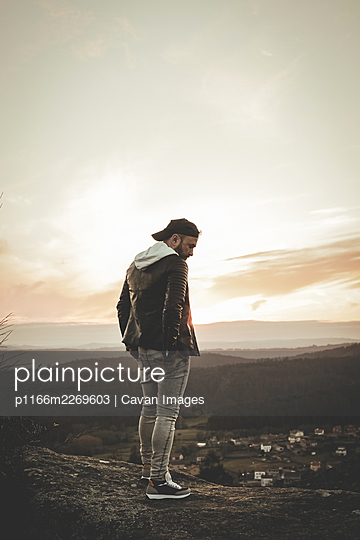 Modern guy wearing sunglasses cap and black windbreaker at sunset - p1166m2269603 by Cavan Images