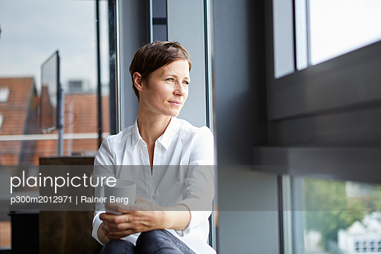 Businesswoman sitting in office with cup of coffee looking out of window - p300m2012971 von Rainer Berg