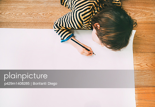 Overhead view of boy drawing on large paper on floor - p429m1408285 by Bonfanti Diego