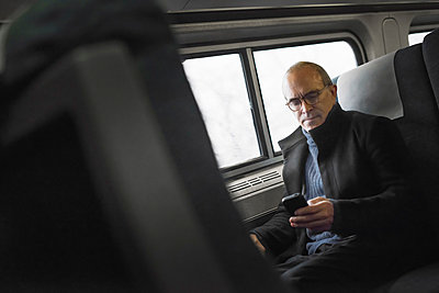 A mature man sitting by a window in a train carriage, using his mobile phone, keeping in touch on the move. - p1100m876837f by Tim Pannell