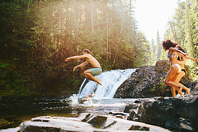 Cheerful friends jumping into river in forest - p1166m1423036 by Cavan Images