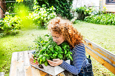 Portrait of young woman with fresh herbs in a box - p300m2029204 by Jo Kirchherr