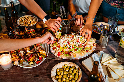 Close-up of friends eating during an outdoor dinner - p300m2155626 by Manu Padilla Photo