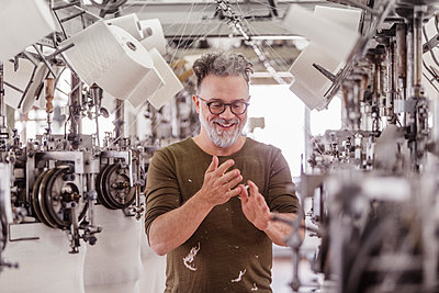 Portrait of a happy mature man in a textile factory - p300m2167473 by Floco Images