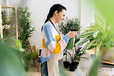 Young woman working in a gardening laboratory or plant shop - p300m2274563 von Giorgio Fochesato