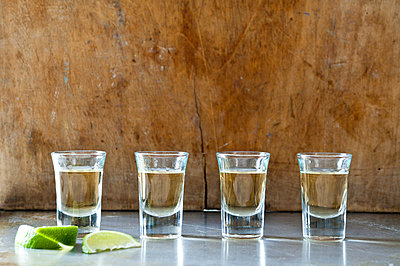Row of tequila shots - p92411945f by David Cleveland