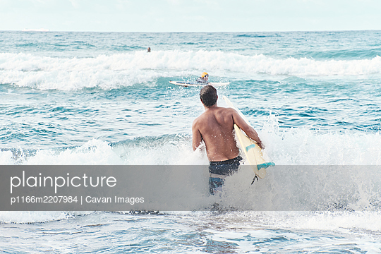 Surfer Going Into The Water For A Surf Session - p1166m2207984 by Cavan Images