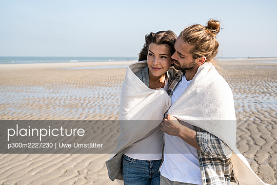 Romantic young couple covered in blanket standing at beach - p300m2227230 by Uwe Umstätter