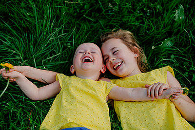 Two laughing sisters lying on a meadow wearing yellow tops - p300m2121718 by Oxana Guryanova