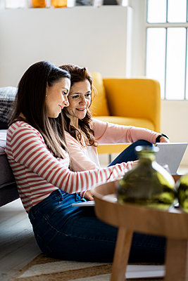 Smiling mother and daughter looking at laptop while sitting in living room at home - p300m2265313 by Giorgio Fochesato