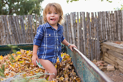 Caucasian boy standing in autumn leaves - p555m1410486 by Marc Romanelli