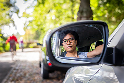 Young man in  car looking into side mirror - p975m2207620 by Hayden Verry