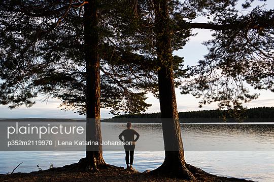 Mature woman standing next to lake - p352m2119970 by Lena Katarina Johansson