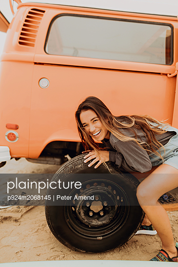 Young woman changing recreational vehicle tyre at beach, portrait, Jalama, California, USA - p924m2068145 by Peter Amend