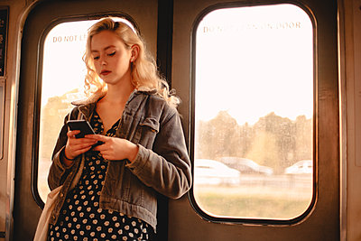 Young woman using smart phone while traveling in subway train - p1166m2153493 by Cavan Images