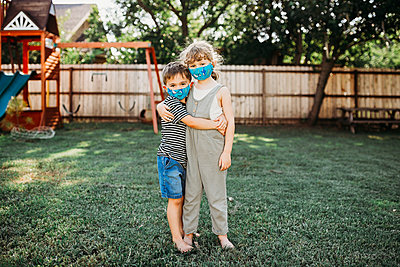 Two young kids hugging outside while wearing homemade fabric masks - p1166m2201691 by Cavan Images