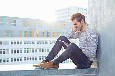 Happy young man sitting on a wall using tablet - p300m2104462 by Philipp Nemenz