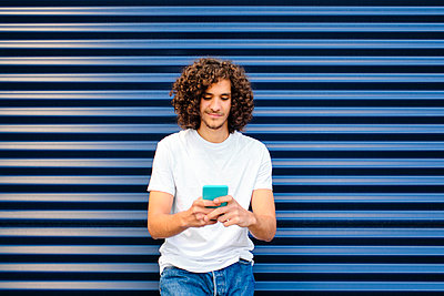 Young man with curly hair using smart phone while leaning on corrugated iron - p300m2273612 by Antonio Ovejero Diaz