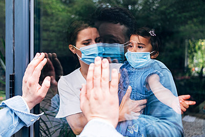 Mother and daughter wearing face masks greeting man through glass during quarantine - p300m2293306 by Angel Santana Garcia