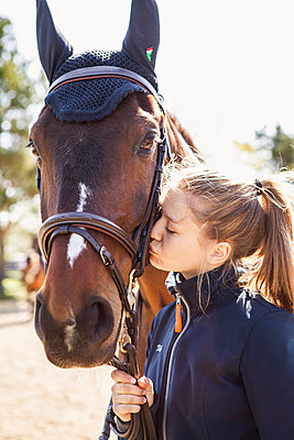 Teenage girl kissing a horse in Sweden - p352m2040651 by Serny Pernebjer
