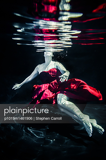 Woman in red dress floating underwater - p1019m1461906 by Stephen Carroll