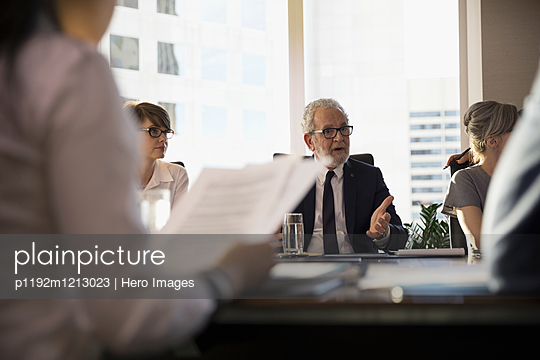 Male lawyer talking and gesturing in conference room meeting