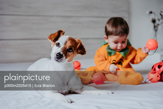 Cute baby boy playing with toy sitting on bed at home - p300m2225415 by Eva Blanco