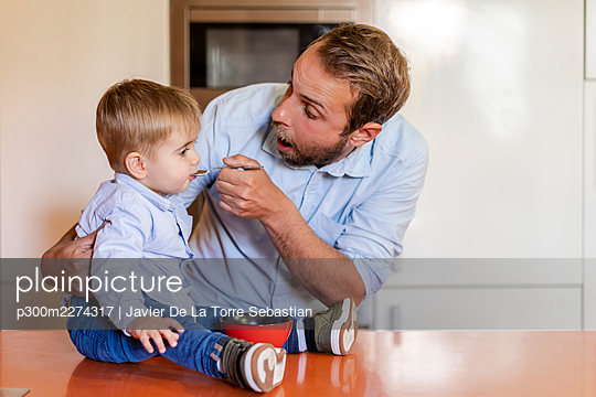 Surprised father feeding son on table at home - p300m2274317 by Javier De La Torre Sebastian