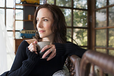 Pensive mature brunette woman drinking coffee looking away - p1192m1174032 by Hero Images