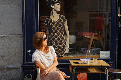 A woman sits in a cafe next to a Audrey Hepburn drawing - p1610m2208783 by myriam tirler
