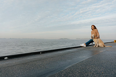 Germany, Hamburg, woman with dog on pier at the Elbe shore - p300m2080406 by Joseffson