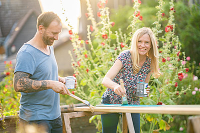 Smiling blond hair woman painting wooden plank with man standing in garden - p300m2264557 by Annika List