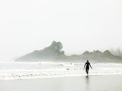 A surfer in a wet suit walks along the water's edge, Cox Bay; Tofino, British Columbia, Canada - p442m1442309 by Ian Grant