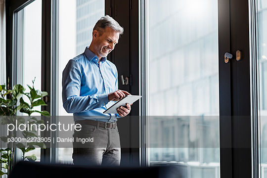 Smiling mature businessman working on digital tablet by window at work place - p300m2273905 by Daniel Ingold
